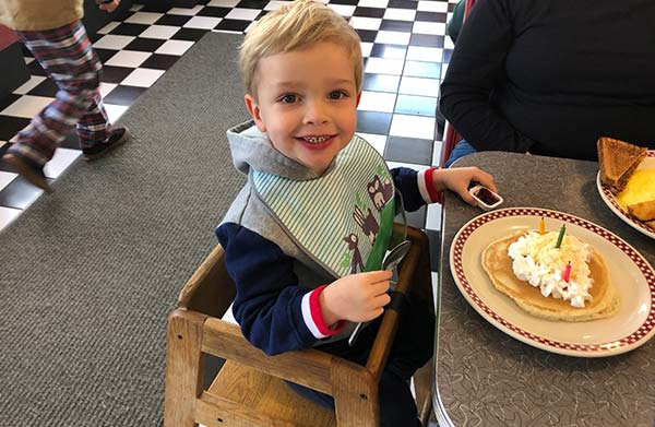 Toddler in highchair with birthday pancake